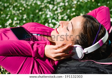 Relaxed female athlete resting and listening music with headphones after workout. Woman lying down and day dreaming on grass and spring flowers. Healthy lifestyle and happiness concept.