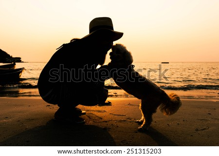 Relaxed woman and dog enjoying summer sunset or sunrise over the sea at the beach.