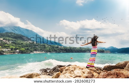 Relaxed woman with open arms from behind on sea. Girl from behind view enjoying in a summer day.  Copay space - copyspace