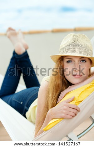 Relaxed young woman with sun hat daydreaming in hammock