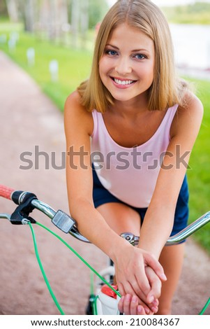 Relaxing after long bicycle ride. Beautiful young blond hair woman smiling and looking at you while leaning at her bicycle