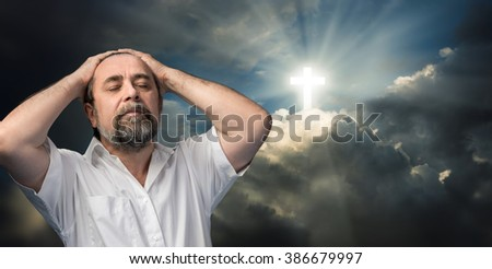 Religious conversion concept. Elderly man thinking about faith and God. Portrait against the sky with a glowing cross symbol of faith.