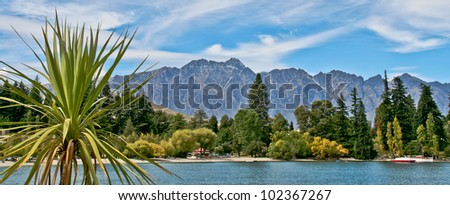 Remarkable Mountains in Queenstown, New Zealand, with closeup of plam tree, and looking over water with boats to view mountain with pretty blue sky