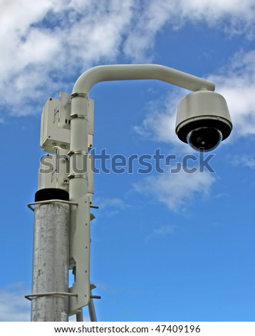Remote surveillance video camera on a post against the sky