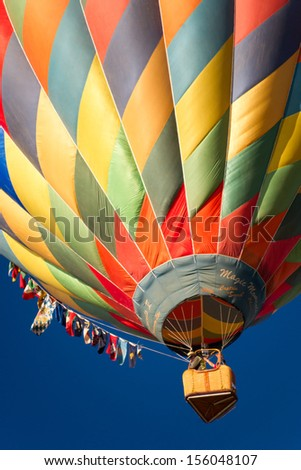 RENO - SEPTEMBER 7: A colorful hot air balloon rises into the clear blue sky during the mass ascension at the 38th annual Great Reno Balloon Race in Reno, Nevada on Sept. 7, 2013