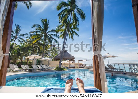 Resort cabana by pool view from lying down perspective with woman's feet by ocean beach with palm trees and sunny blue sky