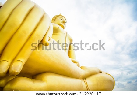 Respect a big golden buddha at the temple in thailand on sunshine day