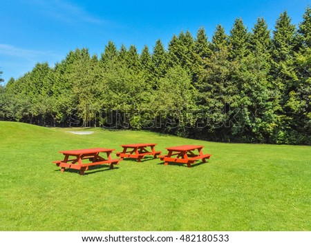 Rest area with red picnic tables on green lawn in a park