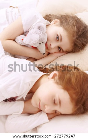 Rest-hour. Two little cute girls lying next to each other on white bed and sleeping with teddy bear toy