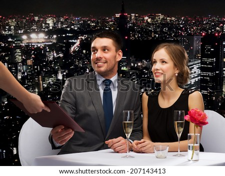 restaurant, couple and holiday concept - waiter giving menu to happy couple at restaurant