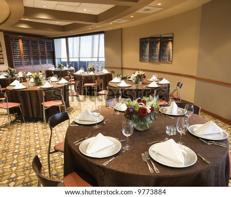 Restaurant interior with table setting and chairs.