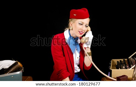 Retro Airline Stewardess or Flight Attendant talking on the Phone While Preparing for Work.
