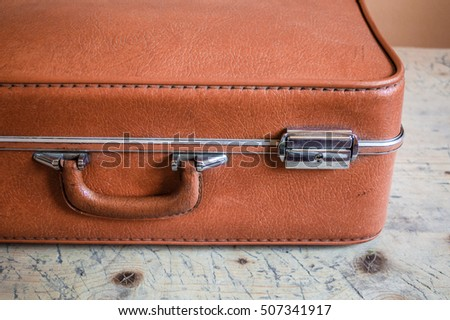 Retro closed orange travel suitcase lying on the wooden surface