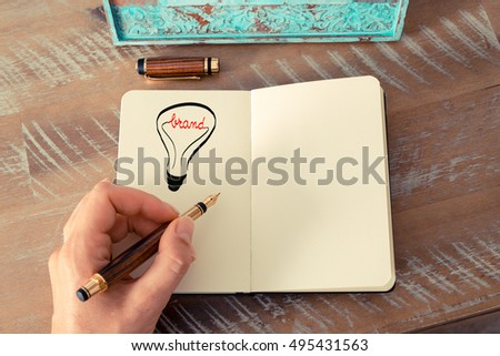 Retro effect and toned image of a woman drawing a lighting bulb with fountain pen on a notebook. BRAND symbol and concept, copy space available for text
