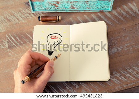 Retro effect and toned image of a woman drawing a lighting bulb with fountain pen on a notebook. Year 2022 symbol for bright idea and business concept, copy space available for text