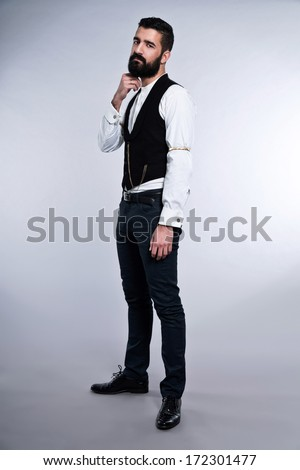 Retro hipster 1900 fashion man with black hair and beard. Studio shot against grey.