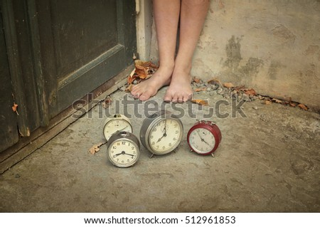 Retro image of alarm clock in the foreground with child feet softly blurry in the background.