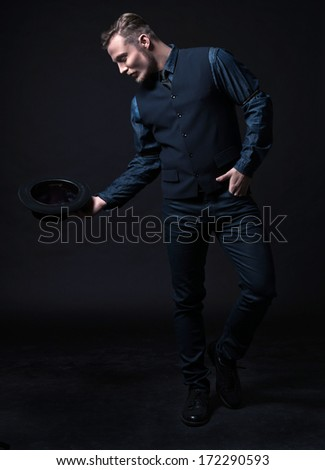 Retro 1900 modern fashion man. Wearing blue jeans shirt with gilet and trousers. Holding black hat. Studio shot against black.