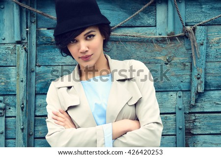 Retro portrait of a beautiful woman. Vintage style. Outdoor fashion photo. Female beauty. Image toned.