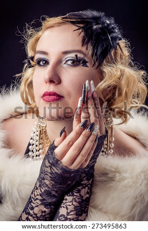 Retro portrait of beautiful blonde woman with gold and pearl jewels and extreme long nails. Gatsby, Vintage style. Isolated on black background