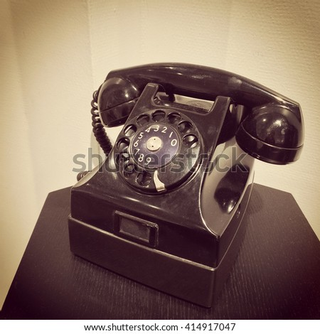 Retro style phone on a table. Sepia toned photo.