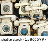 Retro telephones and parts of them on a flea-market floor - stock photo