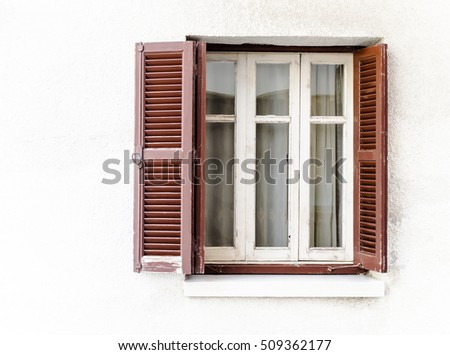 Retro window with brown wooden shutters and curtains at white wall background of the old house. Vintage windows with blinds at english colonial style of buildings on Cyprus.