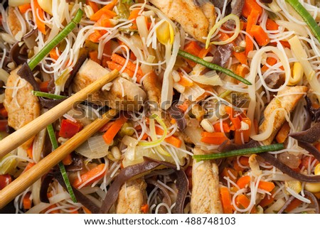 Rice noodles with chicken, mushrooms mun and vegetables, prepared for wook. Top view. Close-up.