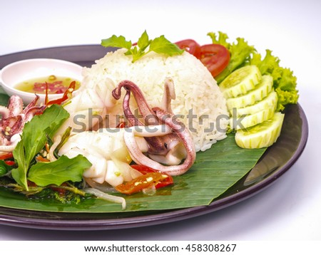 rice topped with stir-fried squid and basil on white background