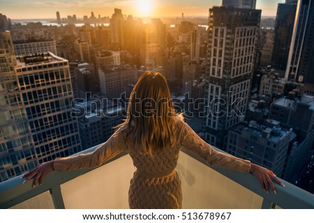 Rich woman enjoying the sunset standing on the balcony at luxury apartments in New York City. Luxury life concept. Successful businesswoman relaxing.