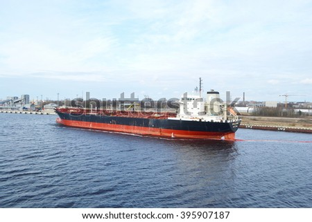 RIGA, LATVIA - APRIL 18, 2015: Cargo ship in the Riga port. Riga - the capital of Latvia and the largest city of the Baltic states with a population of 641,007 people.