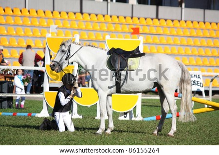 RIGA, LATVIA - SEPTEMBER 25 : An unidentified child falls from pony during Latvian Equestrian Federation cup in pony riding on September 25, 2011 in Riga, Latvia.