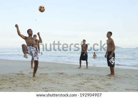 RIO DE JANEIRO, BRAZIL - APRIL 1, 2014: Group of young Brazilians play keepy uppy beach football on Ipanema Beach at Posto 9, a famous gathering place for the game, called altinho locally.