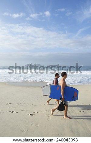 RIO DE JANEIRO, BRAZIL - FEBRUARY 20, 2014: Pair of young Brazilian surfers walk with body boards along the shore of Ipanema Beach.