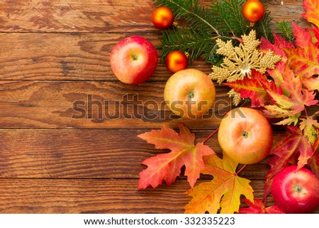ripe apples, colorful maple leaves, fir branch with Christmas ornaments and pine cone on wooden boards. Copy space. Free space for text