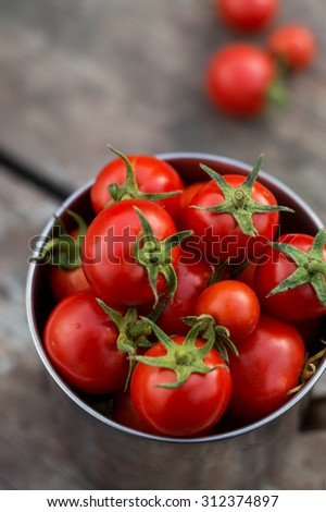 ripe cherry tomatoes on a wooden table in rustic iron cup. top view
