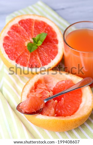 Ripe grapefruits on cutting board, on wooden background