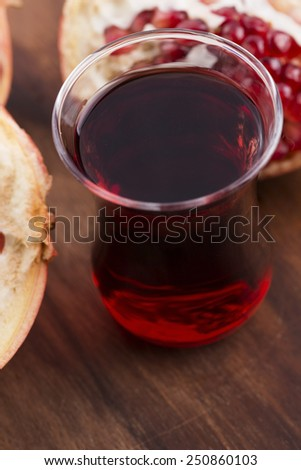 Ripe pomegranates with juice on table