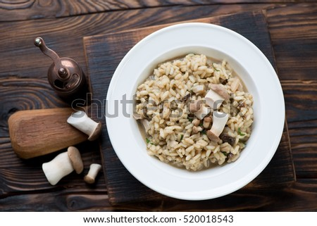 Risotto with porcini mushrooms over rustic wooden background, top view