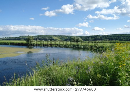 river, land with trees and cloudy sky