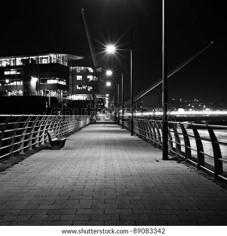 river walkway at night in black and white with river bridge in background