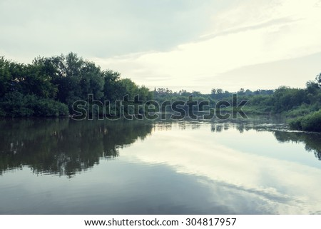 River with reflections in water.Light vintage effect.