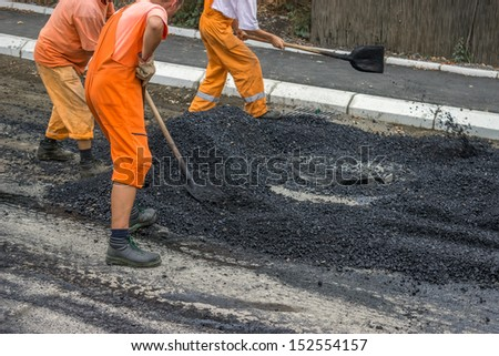 Road construction crew apply the first layer of asphalt