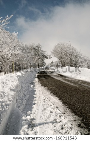 road in the snow with cloudy sky