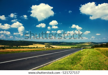 Road on landscape with cloudy sky