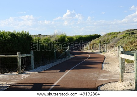 road passing through the bushes and disappearing into the distance to the hills