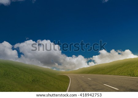 road through green landscape with blue sky and cloudy horizon