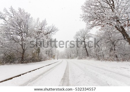 Road with snow covered landscape while snowing in winter season.