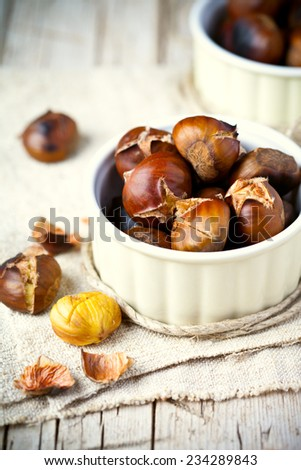 roasted chestnuts in bowls on wooden background