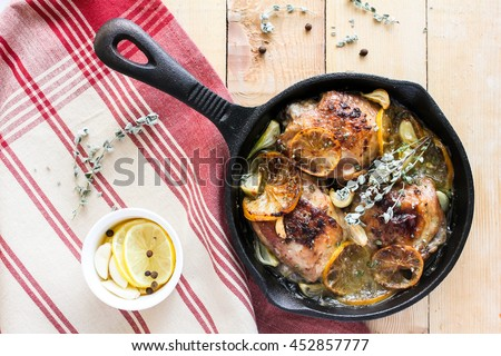 Roasted chicken meat with lemon slices, garlic cloves, thyme and black peppercorns in a pan on a wooden table, top view, selective focus